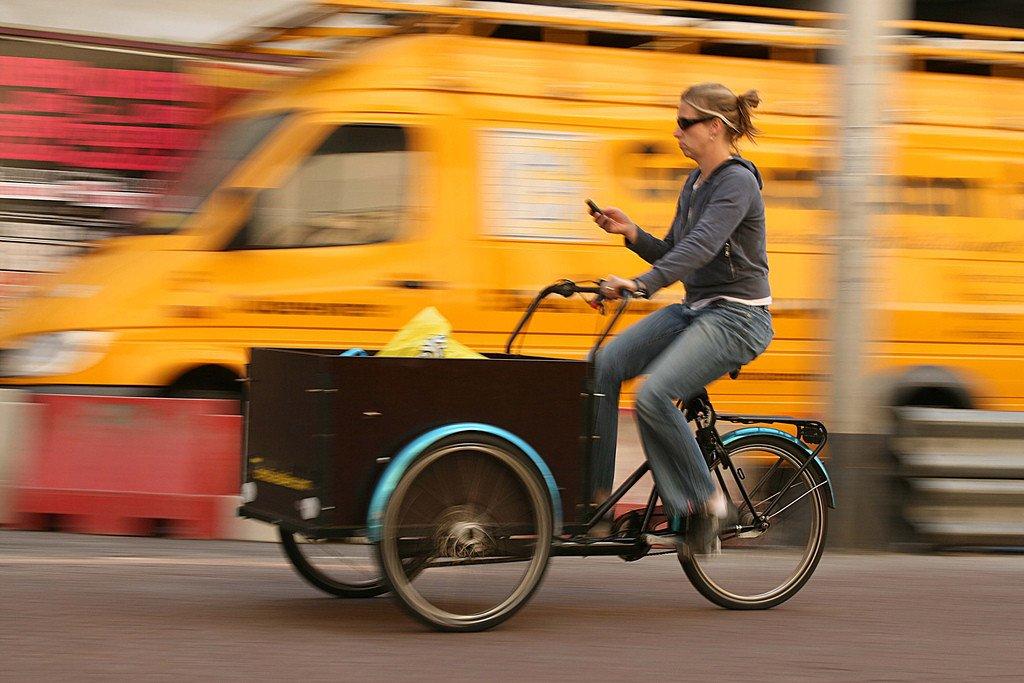 Mujer en bicicleta mirando el móvil