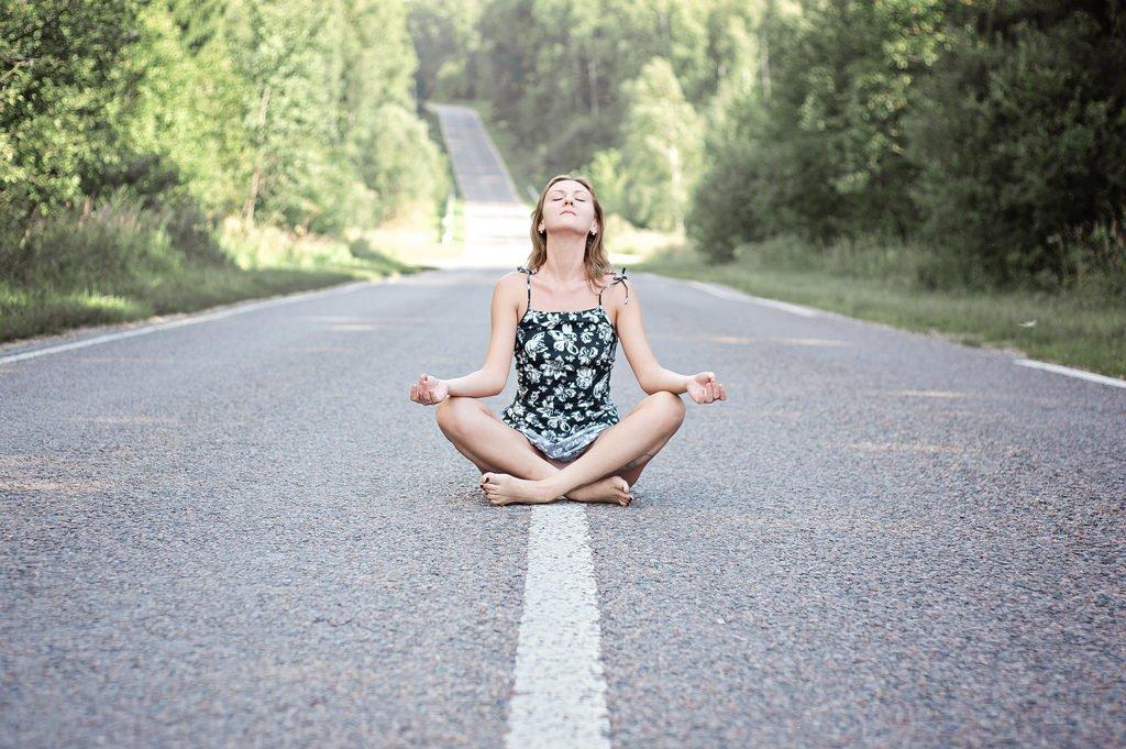 Mujer meditando en la carretera